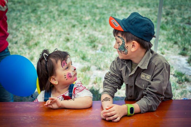 Gullig och rolig pojke och flicka med framsidamålningar på välgörenhetfamiljfestival arkivbild