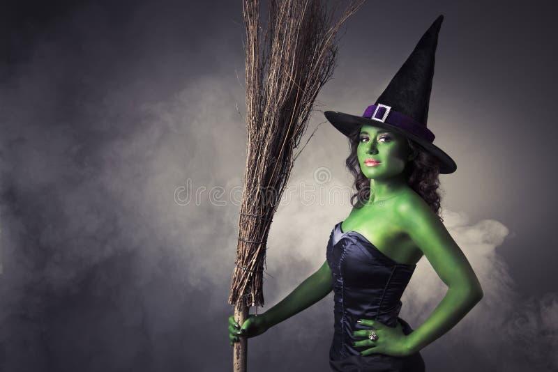 Gullig och sexig Halloween häxa med kvasten arkivfoto