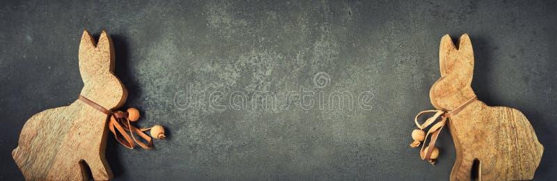 Gullig påskbakgrund med små träkaniner arkivbilder