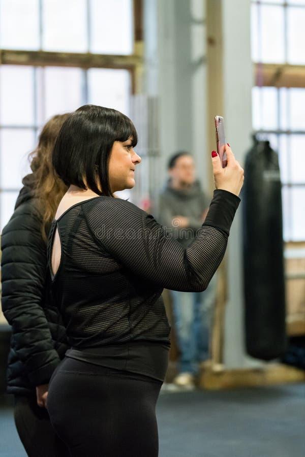 Gullig passformkvinna i svart som tar ett foto med en mobiltelefon royaltyfri fotografi