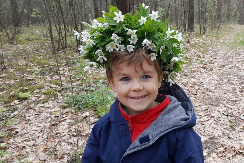 Gullig pojke för stående som ler, krans av blommor på huvudet i vårskog royaltyfri bild