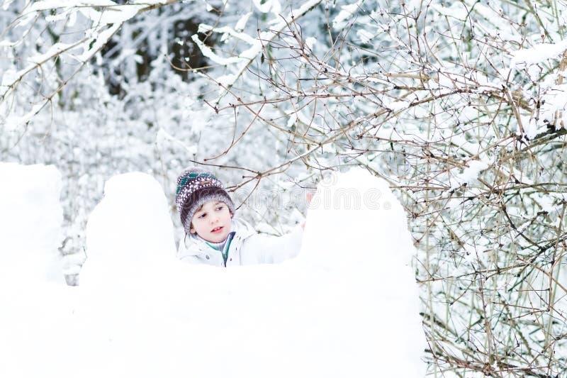 Gullig pojke i det vita omslaget som spelar i ett snöfort royaltyfria bilder