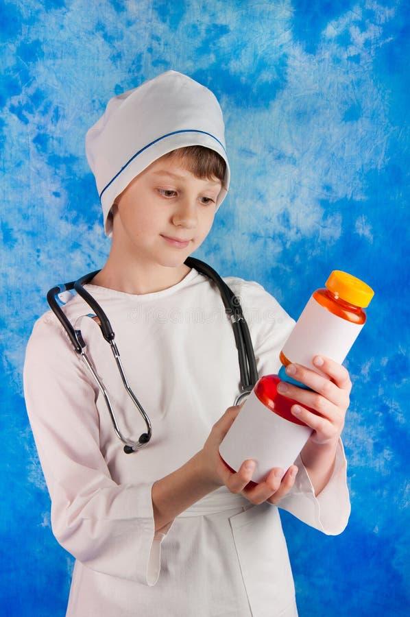 Gullig pojke i doktorsdräkten som ser på preventivpillerflaskor royaltyfri foto