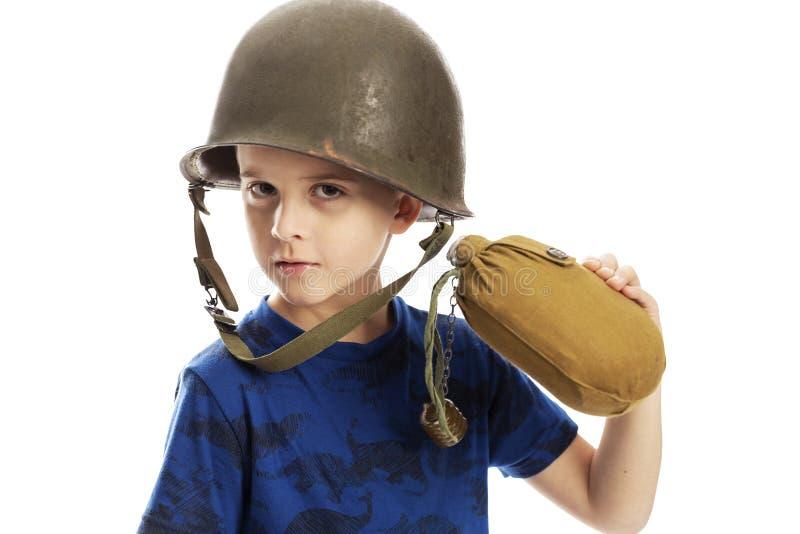 Gullig pojke i en milit?r hj?lm med en flaska i hans hand, n?rbild bakgrund isolerad white fotografering för bildbyråer