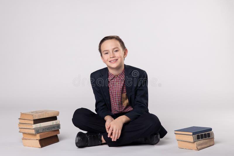 Gullig pojke i ett dräktsammanträde på en vit bakgrund Stapel av böcker arkivbilder