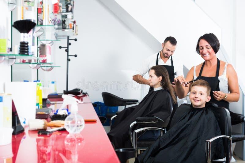 Gullig pojke i grundskolaåldern som får frisyren arkivbild