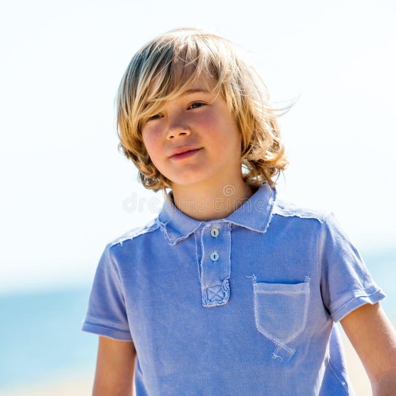 Gullig pojke med den blåa poloskjortan utomhus. arkivfoto