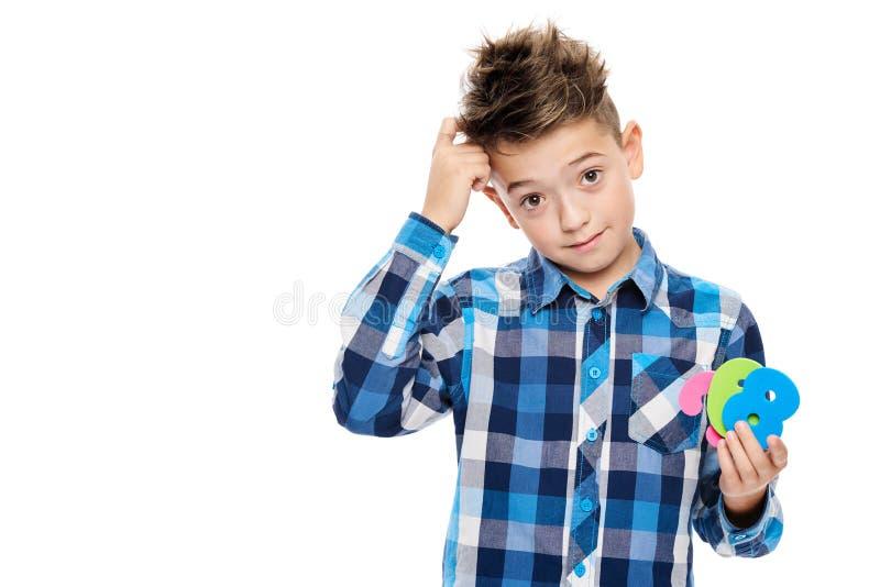 Gullig pojke med dyscalculiaen som rymmer stora färgrika nummer och skrapar hans huvud Lärande handikappbegrepp arkivbilder