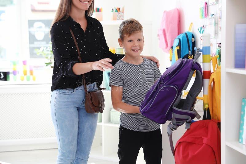 Gullig pojke med modern som väljer ryggsäcken royaltyfria foton