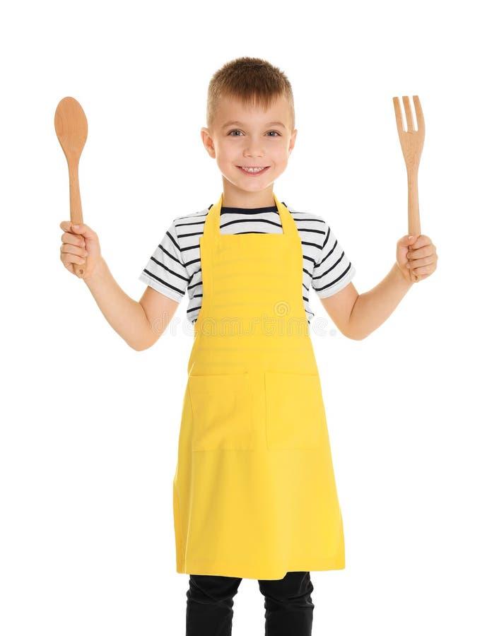 Gullig pojke med träskeden och gaffeln som isoleras royaltyfri foto