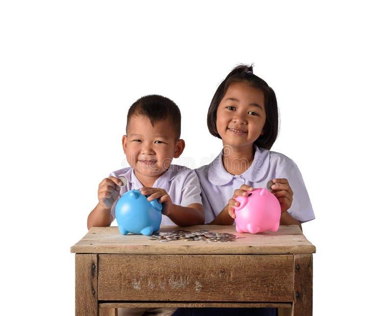 Gullig pojke och flicka för asiatiskt land som sätter mynt in i den isolerade spargrisen på vit bakgrund arkivbild