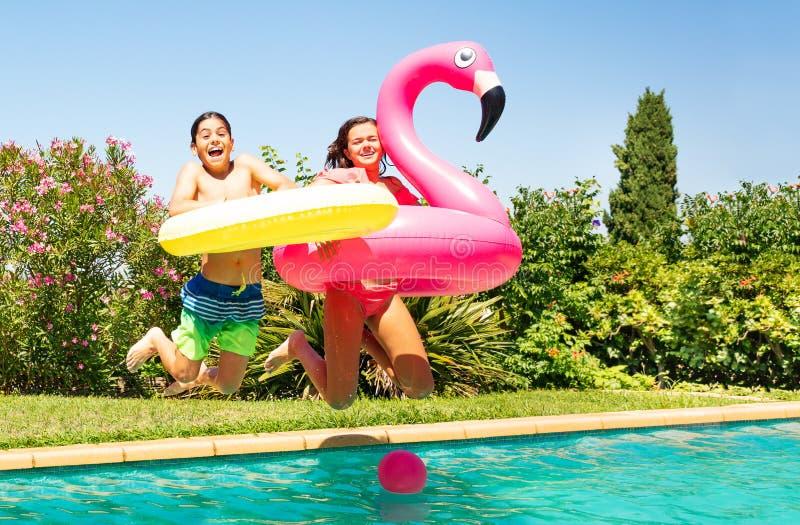 Gullig pojke och flicka som hoppar in i simbassängen royaltyfri fotografi