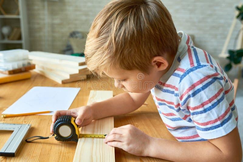 Gullig pojke som arbetar med trä arkivbilder