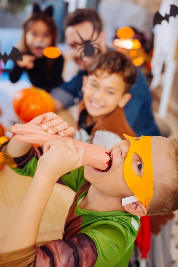 Gullig pojke som bär den Ninja sköldpaddadräkten för allhelgonaaftonen som spelar trick som äter sötsaker royaltyfria foton