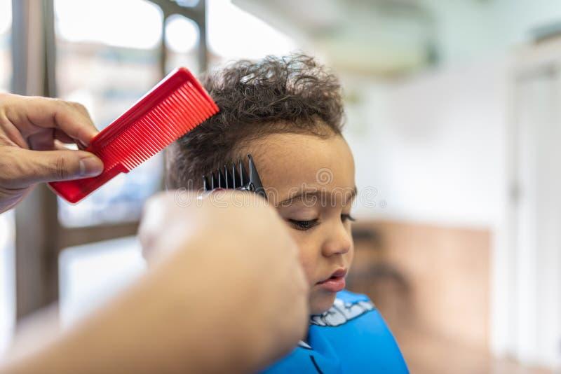 Gullig pojke som får ett hårsnitt i en Barber Shop pärlor för blå för begrepp för bakgrundsskönhet blir grund naturliga over för  arkivfoton