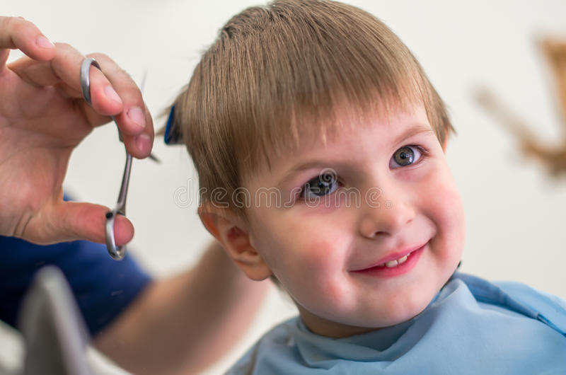 Gullig pojke som får frisyr royaltyfri fotografi