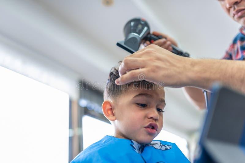 Gullig pojke som f?r ett h?rsnitt i en Barber Shop p?rlor f?r bl? f?r begrepp f?r bakgrundssk?nhet blir grund naturliga over f?r  arkivbild