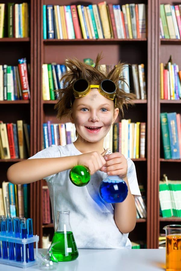 Gullig pojke som gör biokemiforskning i kemi royaltyfri foto