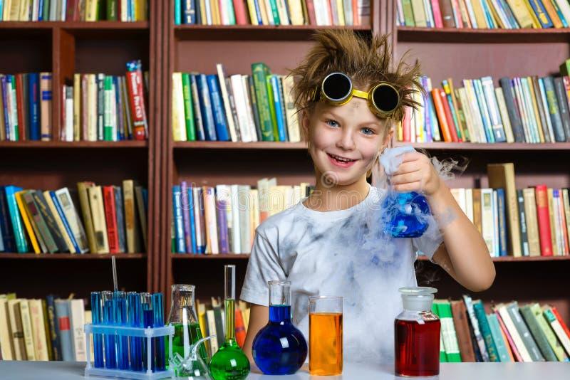 Gullig pojke som gör biokemiforskning i kemi royaltyfri fotografi