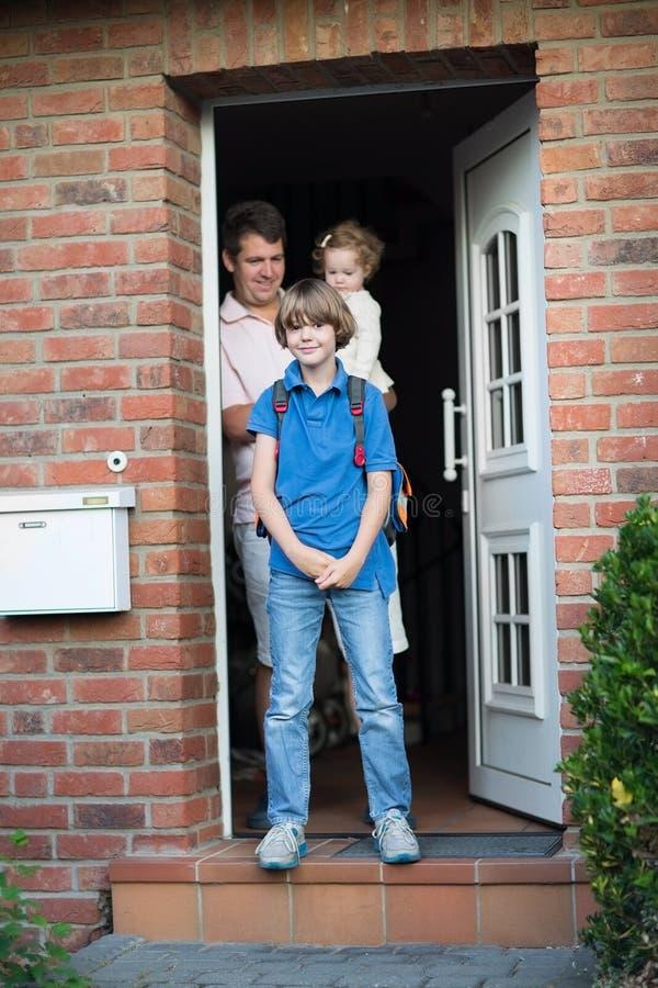 Gullig pojke som hem tillbaka lämnar för hans första dag till skolan royaltyfria bilder
