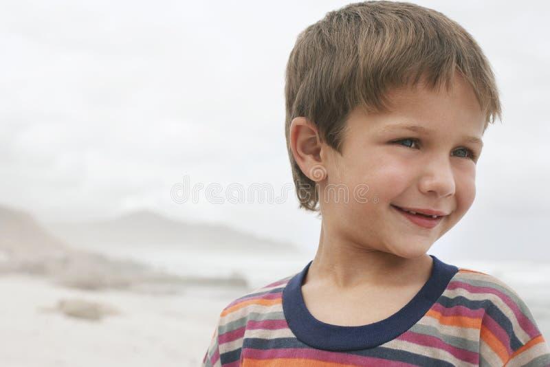 Gullig pojke som ler på stranden royaltyfria foton