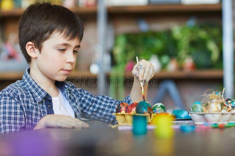 Gullig pojke som målar ägg för påsk fotografering för bildbyråer