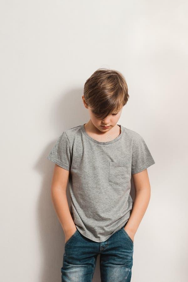 Gullig pojke som ner bugar hans huvud och att luta till den vita väggen fotografering för bildbyråer
