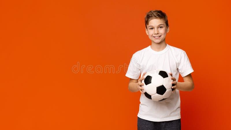 Gullig pojke som rymmer fotbollbollen som ler på orange studiobakgrund royaltyfri fotografi