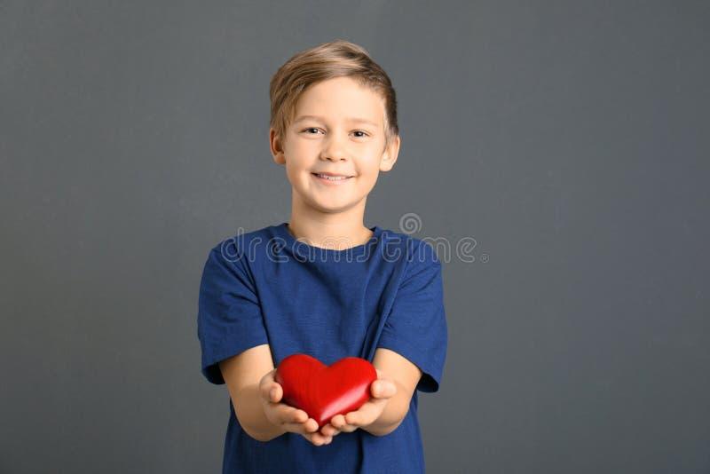 Gullig pojke som rymmer trähjärta på grå färger arkivbilder