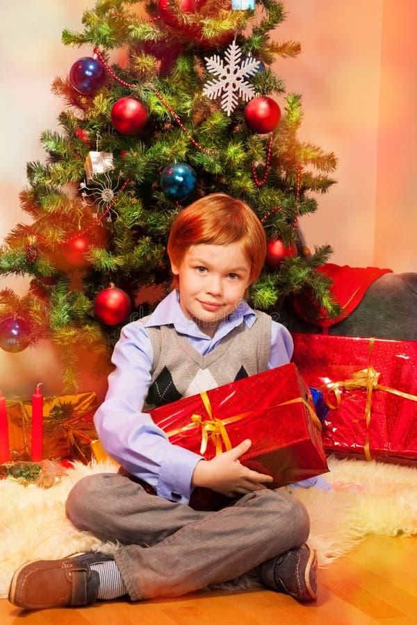 Gullig pojke som sitter nära julgran arkivfoto
