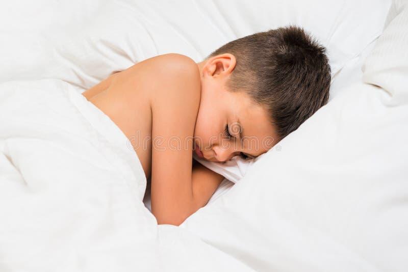 Gullig pojke som sover på säng med det vita arket och kudden caucasian arkivbild