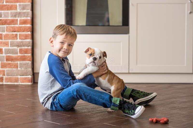 Gullig pojke som spelar med valpengelskabulldoggen royaltyfria foton