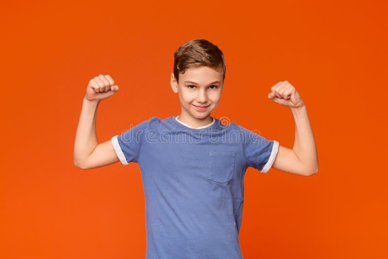 Gullig pojke som visar biceps på orange bakgrund royaltyfri bild