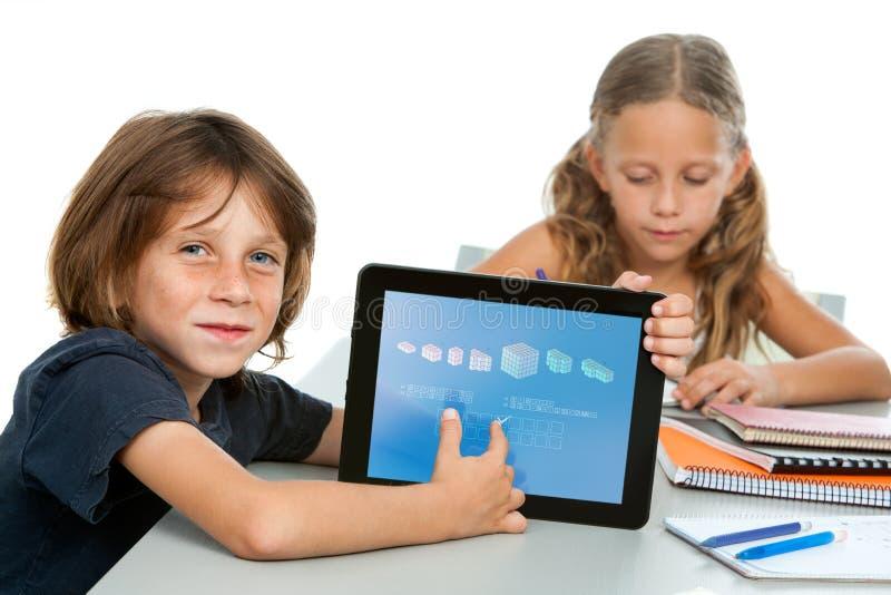 Gullig pojkedeltagare som gör maths på den digitala tableten. royaltyfria bilder