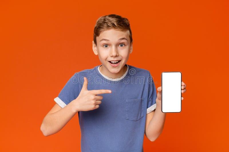 Gullig pojkeman som visar den tomma mobiltelefonsk?rmen arkivbilder