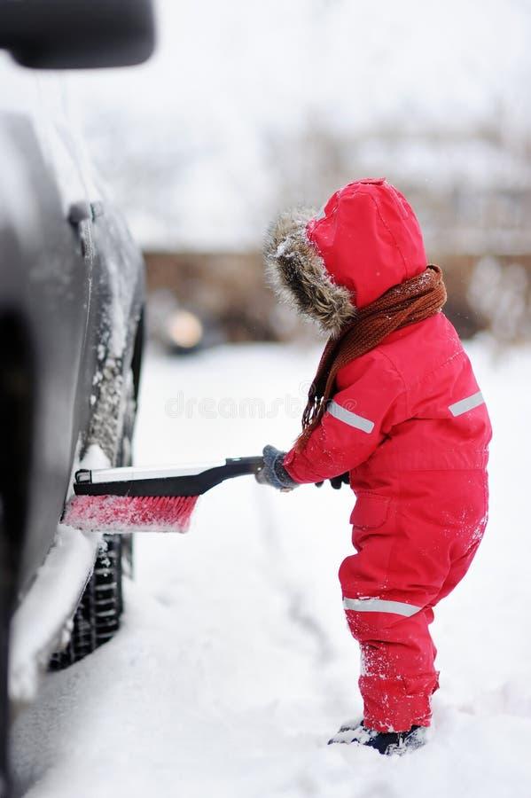 Gullig portion för litet barn som borstar en snö från en bil arkivfoto
