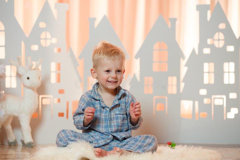 Gullig pys för blont hår i sleepwear nära hus för julleksakpapper arkivbilder