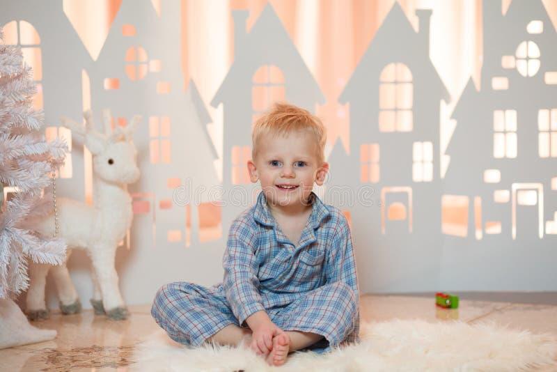 Gullig pys för blont hår i sleepwear nära hus för julleksakpapper royaltyfri foto