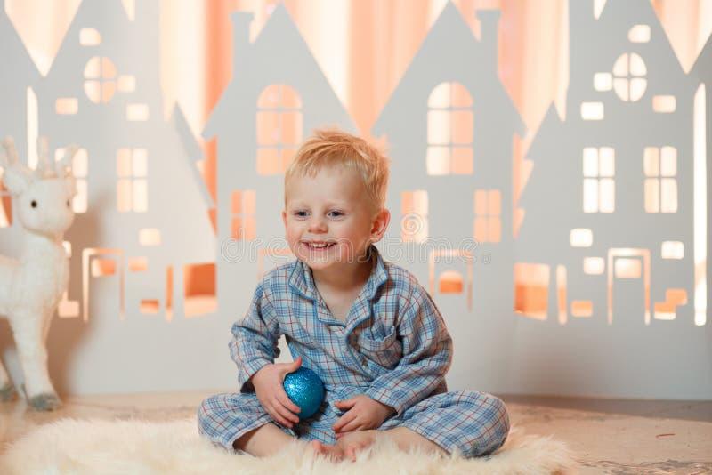 Gullig pys för blont hår i sleepwear nära hus för julleksakpapper royaltyfri fotografi