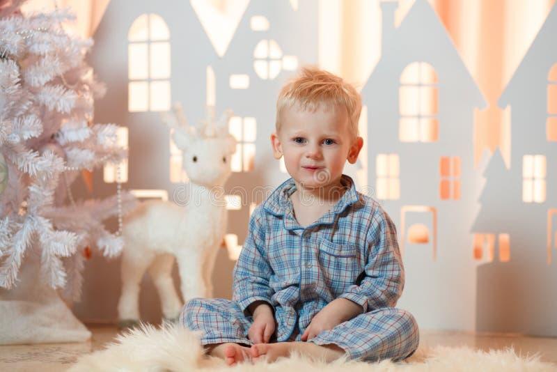 Gullig pys för blont hår i sleepwear nära hus för julleksakpapper royaltyfria foton