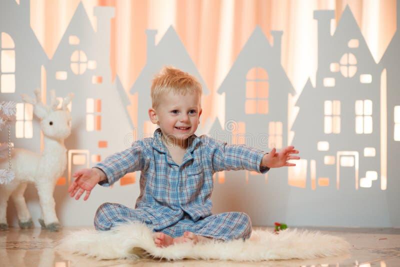 Gullig pys för blont hår i sleepwear nära hus för julleksakpapper arkivbild