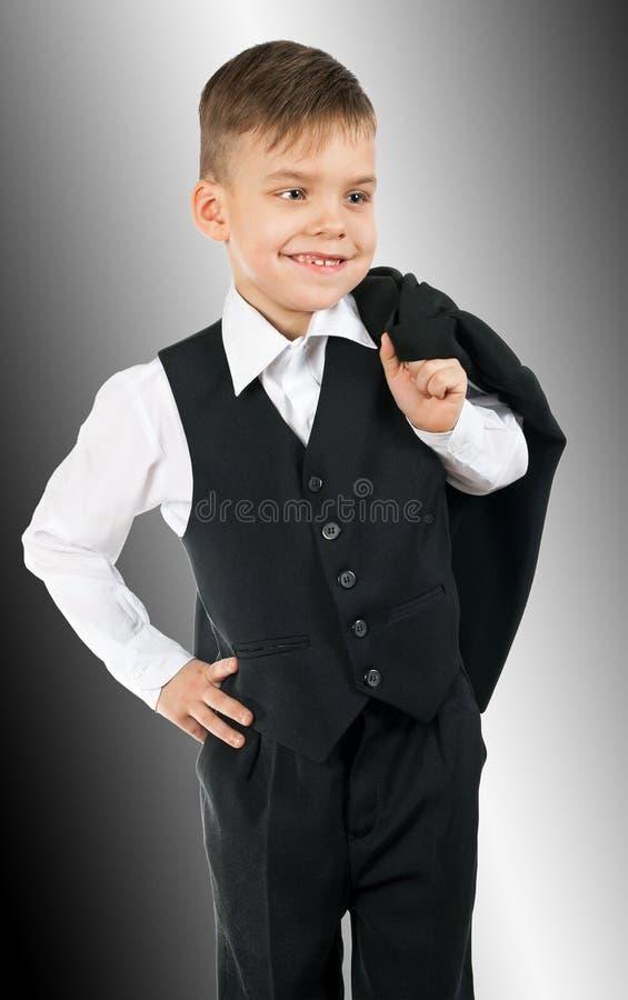 Gullig pys i den vita skjortan och svartvästen royaltyfria foton