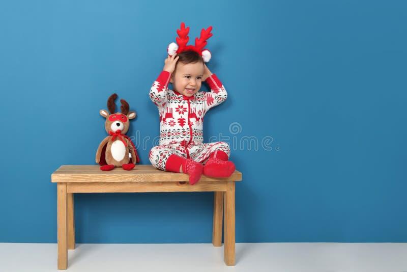 Gullig pys i julpyjamas som sitter på en bänk arkivfoto