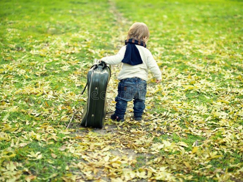 Gullig pys med en stor resväska arkivfoton