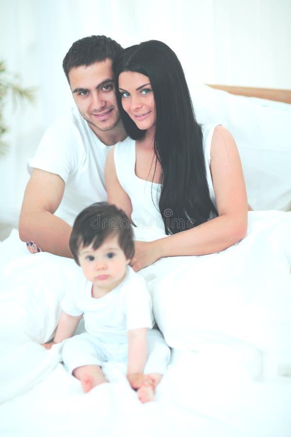 Gullig pys med föräldrar på sängen fotografering för bildbyråer