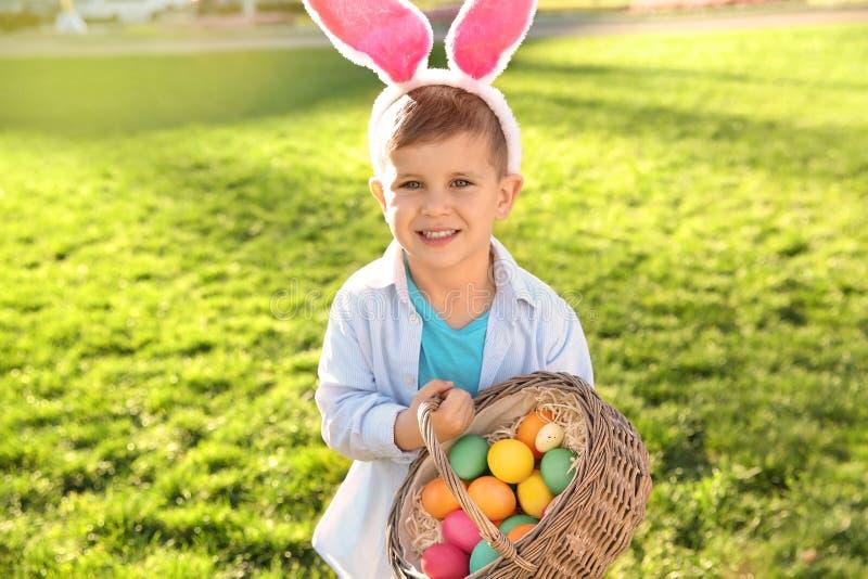 Gullig pys med kaninöron och korgen av påskägg royaltyfria bilder
