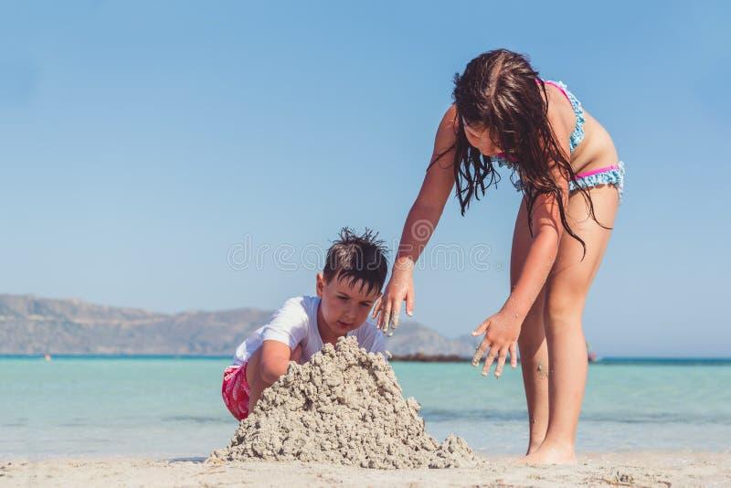 Gullig pys och en flicka som bygger en sandslott på en tropisk havskust royaltyfria foton