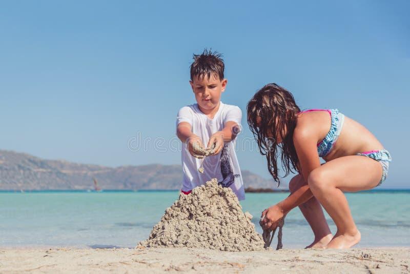Gullig pys och en flicka som bygger en sandslott på en tropisk havskust arkivbilder