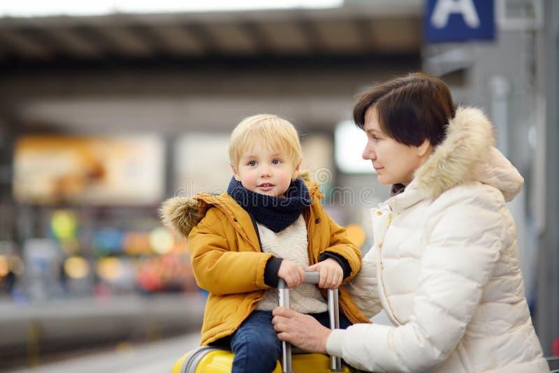 Gullig pys och hans farmor/moder som väntar det uttryckliga drevet på järnvägsstationplattformen royaltyfria foton