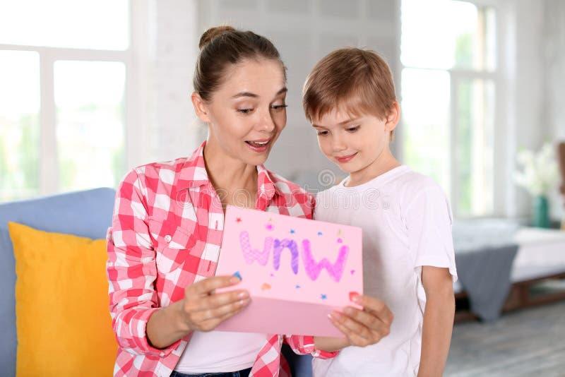 Gullig pys och hans moder med det handgjorda hälsa kortet hemma ber?mdagmamma s arkivfoton